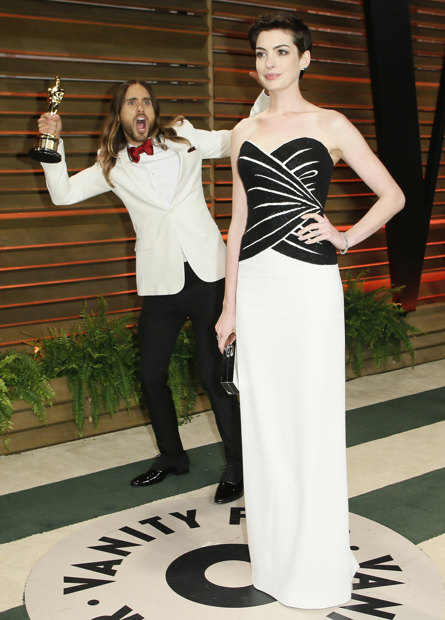 Leto jokes around as actress Anne Hathaway poses as they arrive at the 2014 Vanity Fair Oscars Party in West Hollywood